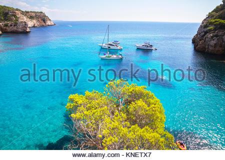 View of yachts anchored in blue sea at Cala Mitjana bay, Menorca, Balearic Islands, Spain - Stock Photo