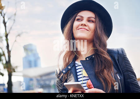 Portrait of young woman in trilby hat in city - Stock Photo