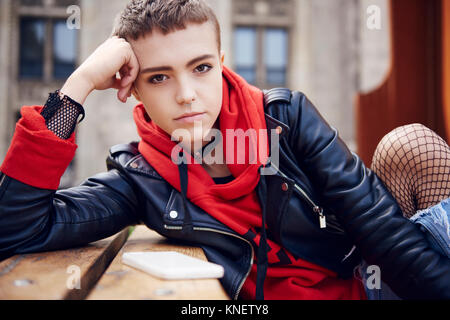Portrait of cool young woman with short hair at city bench - Stock Photo