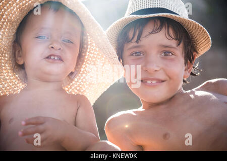 Portrait of boy and toddler brother on beach wearing sunhats, Begur, Catalonia, Spain - Stock Photo