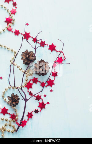 Pine cones, garlands, tree branches on a white wooden background. Christmas decorations concept. - Stock Photo