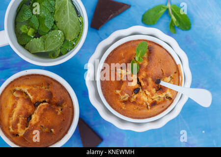 Chocolate cupkakes with mint tea, blue background, top view. Sweet home-cooked concept. - Stock Photo