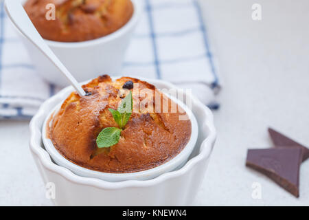Homemade cupcakes with chocolate in a white ceramic bowl. - Stock Photo