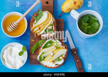Sandwiches with cottage cheese, honey, pear and walnuts with a mint tea. European healthy festive breakfast concept. - Stock Photo