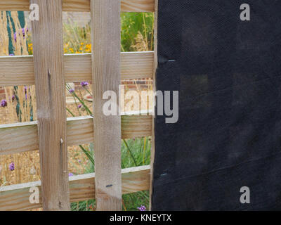 OPEN GARDEN TRELLIS WITH BLACK FABRIC STAPLED TO INSIDE THUS SHIELDING VIEW OF OIL TANK SITUATED IN REAR GARDEN - Stock Photo