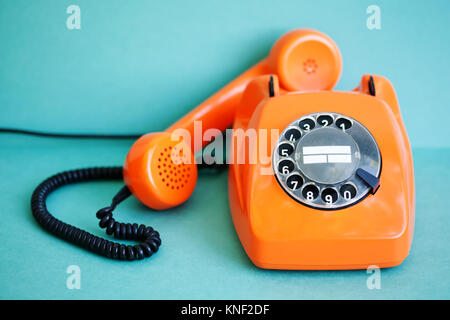 Busy retro phone orange color, handset receiver on green background. Shallow depth field photography - Stock Photo