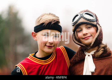 Portrait of boy and twin sister wearing basketball and pilot costumes for halloween - Stock Photo