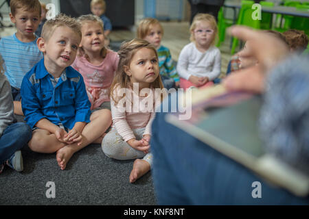 Young children sitting on carpet in classroom, listening to teacher at front of class - Stock Photo