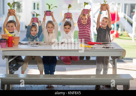 Girls and boys at preschool, portrait holding up pot plants at picnic table - Stock Photo