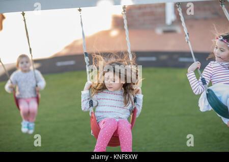 Girls at preschool, swinging on playground swings in garden - Stock Photo