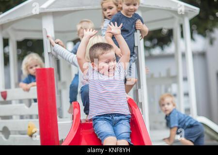 Boys and girls at preschool, sliding on playground slide in garden - Stock Photo