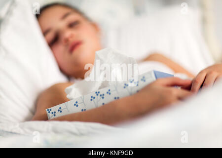Girl in bed holding box of tissues - Stock Photo