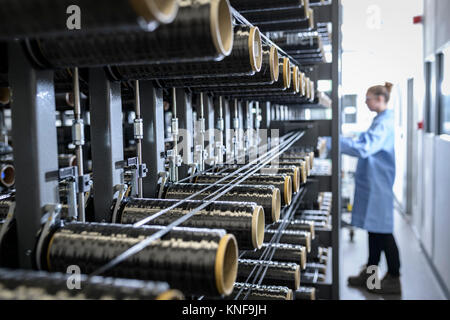 Operator with carbon fibre bobbins on loom in carbon fibre production facility - Stock Photo