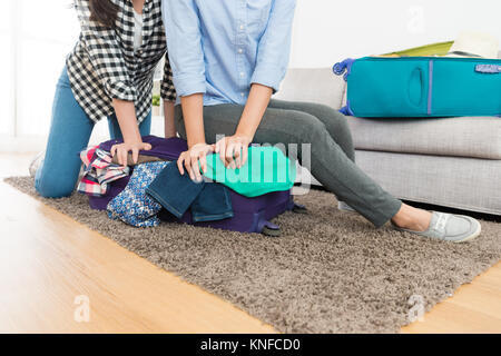 young woman sitting on overweight and overfilled baggage suitcase trying to close luggage while packing bag with - Stock Photo