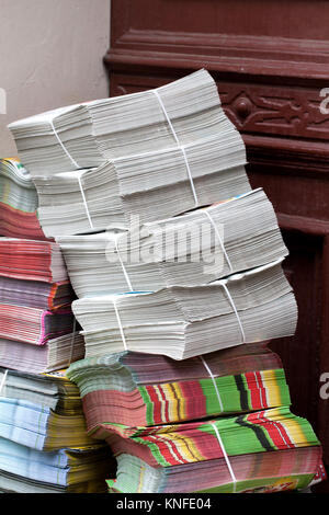 stack of newspapers ads lying on the threshold of the house - Stock Photo
