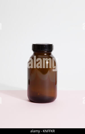 an old vintage pharmacy glass bottle on a vibrant pop pink background. Minimal color still life photography - Stock Photo