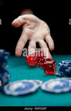 Image of man throwing red dices on table with chips in casino, - Stock Photo