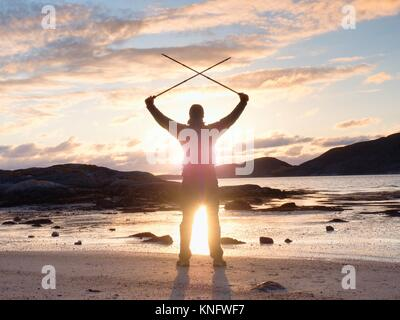 Man hiker with a backpack and trekking pole standing at rocky shore and looking on the evening horizon. Sun flare - Stock Photo