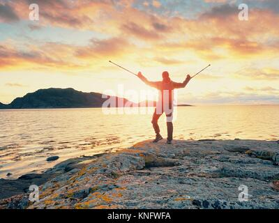 Man tourist with backpack and medicin crutch  standing on rocky beach. Hiker enjoy empty beautiful shore in sunrise - Stock Photo