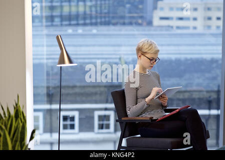 Caucasian businesswoman in a contemporary office tapping the screen of a mobile device - Stock Photo