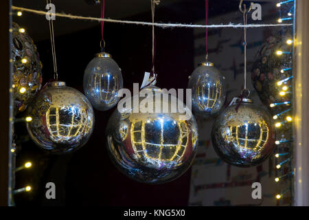 Christmas baubles hanging in a shop window at night in Chipping Campden, Cotswolds, Gloucestershire, England - Stock Photo