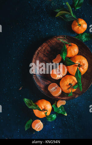 Citrus fruits on a wooden plate with green leaves. Vibrant tangerines on a dark background. Rustic food photography.