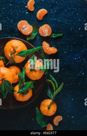 Citrus fruits on a wooden plate with green leaves. Vibrant tangerines on a dark background. Rustic food photography. - Stock Photo