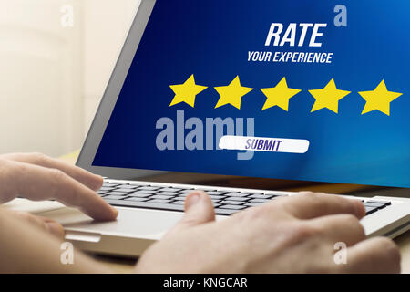online scoring concept: man using a laptop with rating interface on the screen. Screen graphics are made up. - Stock Photo