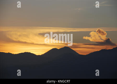 Early morning at Lake Atitlan in Guatemala which is surrounded by high cliffs and overlooked by three volcanoes - Stock Photo