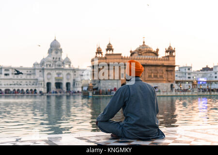 Wide angle picture of Indian man wearing orange turban praying in front of the holy lake at Sri Harmandir Sahib, - Stock Photo