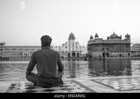 Black and white picture of the back of Indian man praying in front of the holy lake at Sri Harmandir Sahib, known - Stock Photo