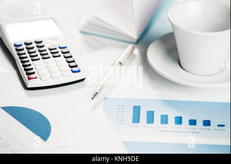 Calculator with financial charts on a table with coffe cup - Stock Photo