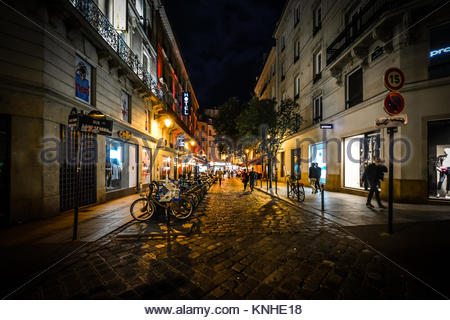 A row of bicycles for rent on a colorful street in the Latin Quarter of Paris France late at night - Stock Photo