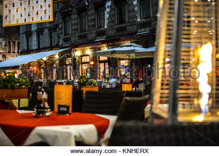 A patio at an outdoor cafe is heated by a flame heater late at night in Diocletian's Palace tourist section of Split - Stock Photo