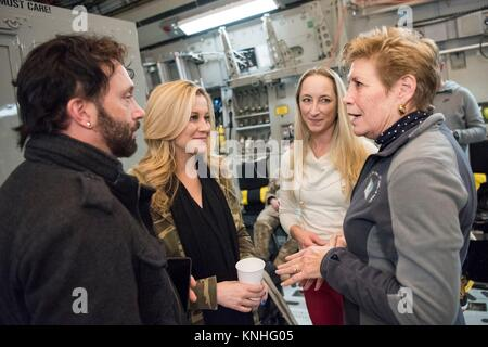 Guitarist Dave Baker (left) and country music singer Kellie Pickler talk to USO event organizers upon arriving for - Stock Photo