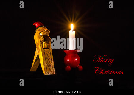 Christmas greetings in English on a Norwegian Gnome Handcarved Wooden Nut Cracker, together with a candlelight on - Stock Photo