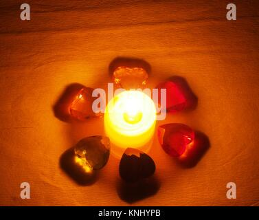 Burning candle lying around it is transparent with colored stones in the form of hearts. Still life - Stock Photo