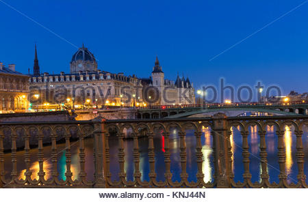 Conciergerie Building in Paris, France at night with lights reflection in the Seine River water. - Stock Photo