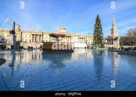 London, UK. 12th Dec, 2017. Ice covers part of Trafalgar Square fountains which has frozen due to the cold temperatures - Stock Photo