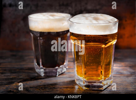 Two big glasses with freshly poured dark and light beer and head of foam on wooden desk. Food and beverages concept - Stock Photo