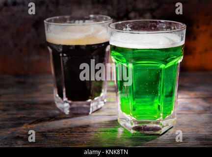 Two big glasses with freshly poured dark and green beer on wooden desk. Food and beverages concept - Stock Photo