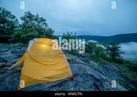 A tent on a rock ledge of Anthony's Nose in the Hudson Highlands of New York State early in the morning with a low - Stock Photo