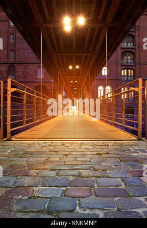 Speicherstadt, or warehouse district in Hamburg at night. Historical footbridge towards the old warehouse building - Stock Photo