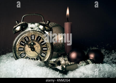 Old alarm clock showing five to midnight and a candle on a  New Year's Eve - Stock Photo