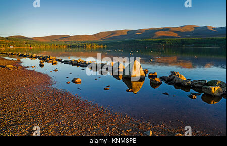 Reflections on Loch Morlich, Cairngorms National Park, Scotland Highlands, on a calm sunny autumn afternoon - Stock Photo