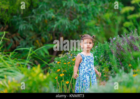 young brunette girl in blue dress standing in pretty flower garden - Stock Photo