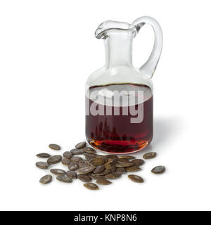 Bottle with pumpkin seed oil and roasted seeds on white background - Stock Photo