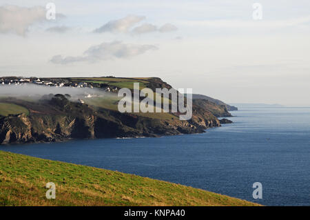 Mist rolls down the Fowey estuary over Polruan on a calm winter day in Cornwall. - Stock Photo