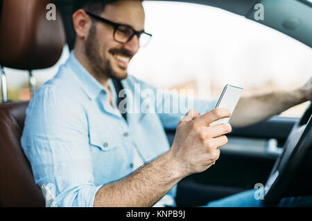 man using phone while driving the car - Stock Photo