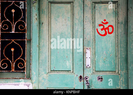 Om-sign on a green door - Stock Photo